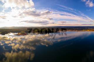 Drone aerial view of a lake reservoir of a dam with perfect reflection on the water of the sky in Sabugal, Portugal