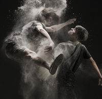 Creative dancers jumping in studio with powder