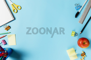 Flat lay with school concept on blue background with schooling accessories
