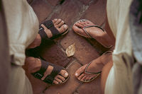 Top down view of man and woman wearing sandals and flip flops facing eachother. Summertime, adventure, backpacking, traveling concept.