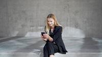 Glad businesswoman using mobile phone