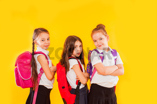 Cute girls in uniform with backpacks on yellow background