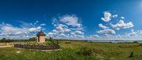 Small religious Christian chapel on ukrainian village outskirts near  lake. Sunny, summer day.