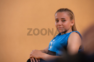 a portrait of a woman with a disability sitting in a wheelchair waiting for a basketball game to begin