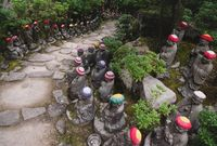 Stairs surrounded by Buddha statues with knitted hat offerings at the temple Diasho-in in Miyajima, Hiroshima, Japan
