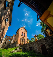 Grodno Castle surrounded by greenery under the sunlight and a blue sky in Zagorze, Poland
