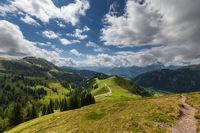 Wanderweg durch schöne Alpenlandschaft unter blauem Wolkenhimmel