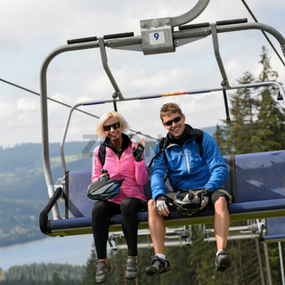 Young couple sitting on chairlift