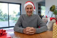 Caucasian senior man wearing santa hat having video call at christmas time
