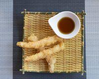 three prawns tempura with sauce on yellow bamboo plate