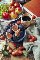 Dish with figs, apples and grapes and a cup of coffee on a wooden background with warm cozy knitwear, autumn leaves and apples.
