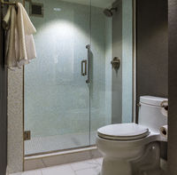 Modern hotel bathroom with glass wall shower and toilet
