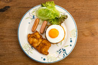 Top view of thai style american fried rice with green vegetables, sausages, fried egg, fried chicken and raisin in white ceramic dish.
