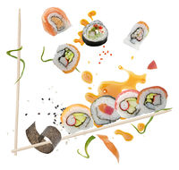 sushi rolls and ingredients with wooden chopsticks  on white background