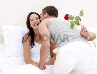 Man giving a rose and a kiss to his beautiful wife