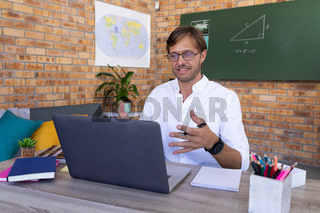 Caucasian male maths teacher giving online lesson sitting at laptop talking