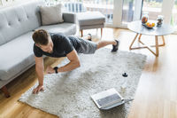 Handsome young man working out at home in the living room