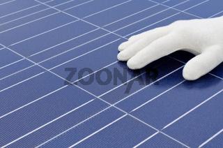 Hand mit weissem Handschuh vor Solarzellen