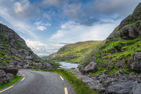 Winding road running through Gap of Dunloe with view on lake and green hills, Black Valley