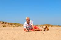 Senior man with old dog at beach