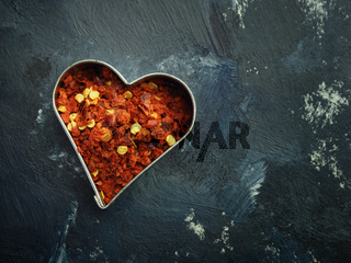 Hot organic chili flakes in a heart shaped cookie cutter, top view