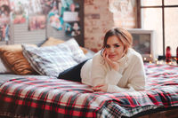 Young woman resting on bed against retro posters