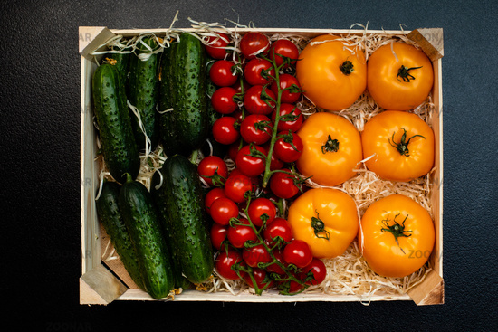 Delivery of fresh tomatoes and cucumbers in a wooden box