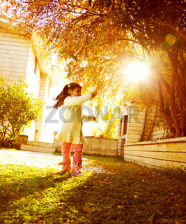 Small girl in sunny autumn day