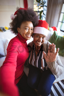 Smiling african american adult daughter and senior mother in santa hats taking christmas selfie