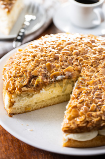Sliced sweet almond cake. Pie with cream and almonds.