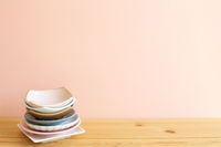Stack of colorful dishes on wooden table. Pink background