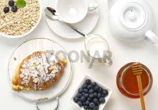Raw oatmeal in white ceramic plate, blueberry, honey on white table, breakfast