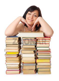 Young smiling woman with heap of books