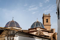 The main church 'San Roque' with blue tiled domes and tower from the 18th century in Oliva, Spain