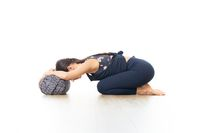 Restorative yoga with a bolster. Young sporty attractive woman in bright white yoga studio, lying on bolster cushion, stretching and relaxing during restorative yoga. Healthy active lifestyle