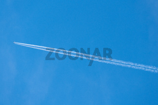 Contrail behind a aircraft jet liner on a clear blue sky day