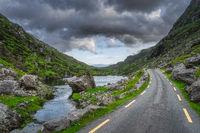 Winding road running through Gap of Dunloe with stone Wishing Bridge in distance, Black Valley