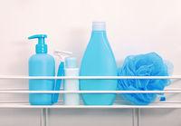 Blue bottles of hygiene toiletries in white bath