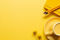 Notebook, pencil, coffee cup on yellow background. flat lay, top view, copy space. workspace