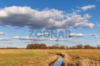 Blauer Himmel mit Wolken über der Oberalsterniederung mit Wiesen und der Alster