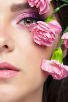 Closeup portrait of female face with pink beauty makeup and carnation flowers on the temple.