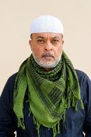 Portrait of handsome bearded muslim man against plain wall