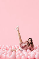 Funny smiling woman lying in many pink balloons with her legs up