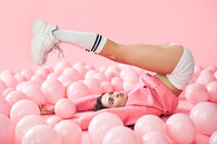 Young pretty woman have fun with legs up lying in pink balloons over pink pastel background