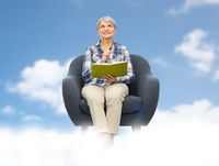 smiling senior woman in armchair writing to diary