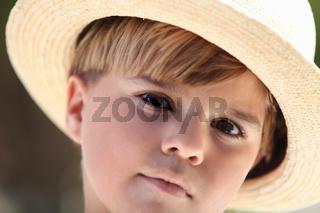 little boy wearing a straw hat