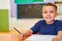 Fröhlicher Junge beim Lernen in der Grundschule