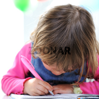 Little cute blond baby girl is drawing with pencil on paper
