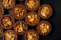 Delicious chocolate tartalets with caramel cream and nuts