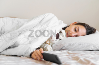 Young woman goes to sleep with teddy bear in her bedroom. Phone addiction, insomnia. Checking social media. Circadian rhuthm.
